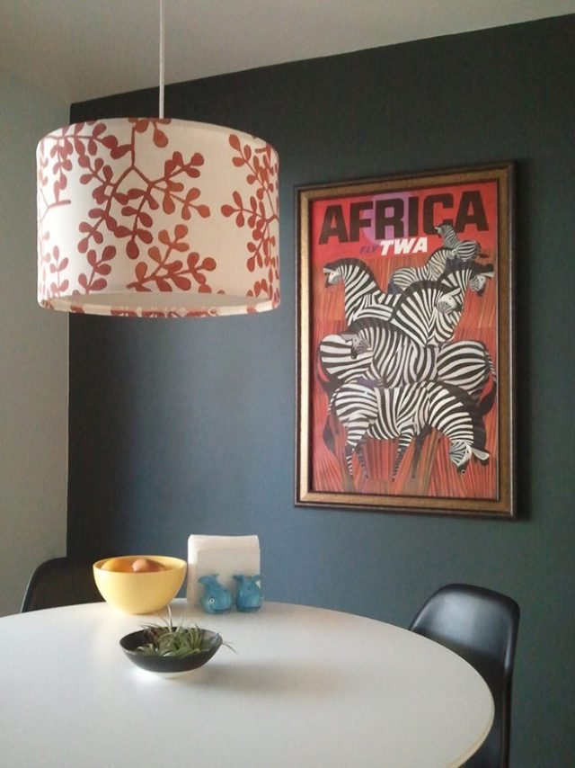 Corner with white dining table, chairs and dark grey painted wall hung with a framed vintage TWA Africa poster