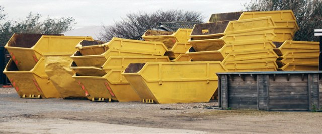 Large number of large yellow skips stacked one on top of another