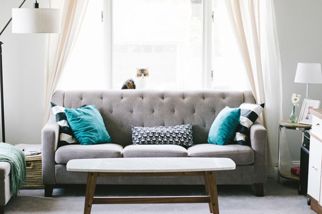 Grey buttoned sofa in front of white curtains