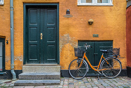 orange bicycle outside a building with black double doors