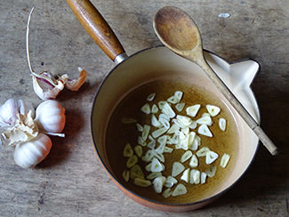 Finely sliced garlic and olive oil in a saucepan | H is for Home
