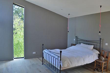 Bedrom with grey walls, tall feature window and wooden floor with underfloor heating