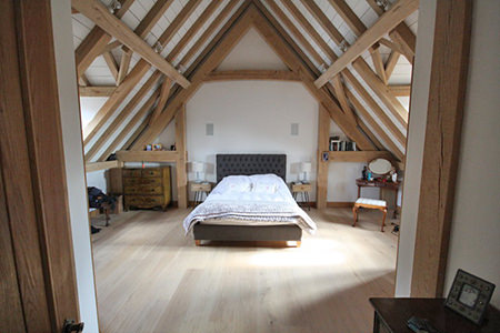 barn conversion loft bedroom with wood floor and underfloor heating