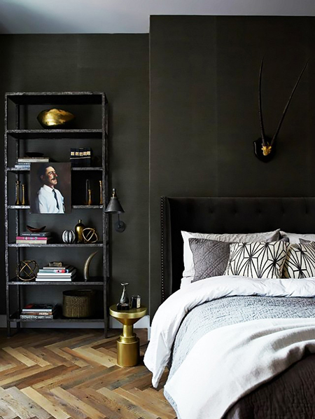 Bedroom with black painted walls and brass accessories