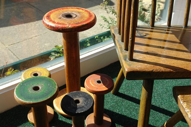 Collection of wooden vintage bobbins in the window of our new shop space | H is for Home