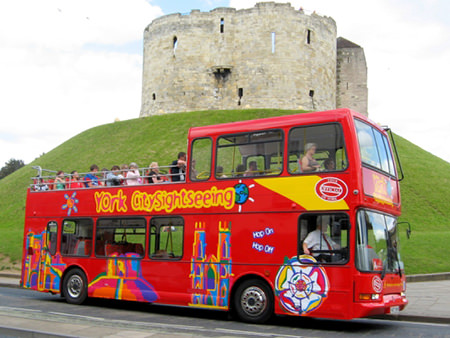Red York CitySightseeing bus in front of York Castle