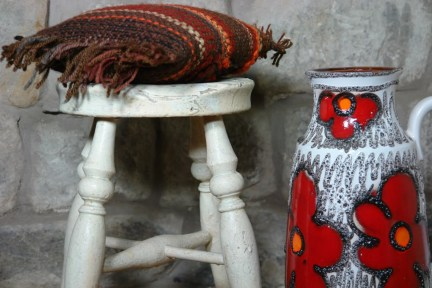 Floral West German vase with rustic stool and knitted cushion
