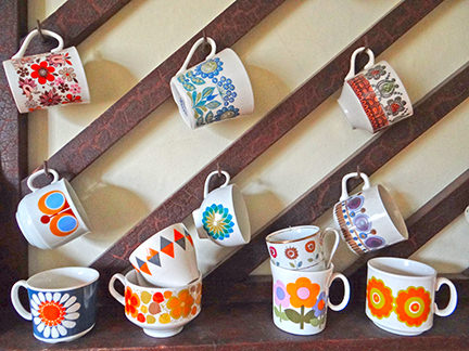 Vintage cups on an antique wooden rack