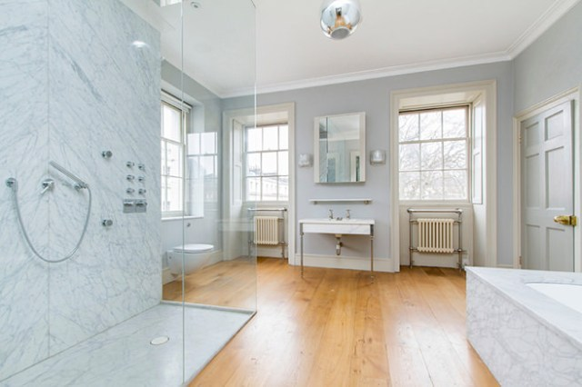 Modern bathroom with pair of cast iron radiators beneath windows