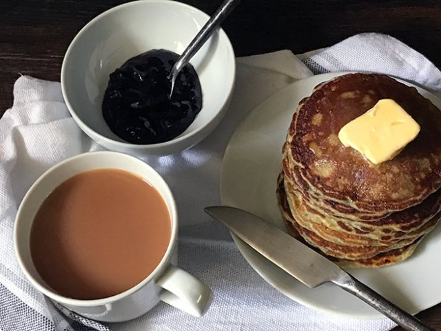 Stack of jammy cornmeal griddle cakes with butter pat on top