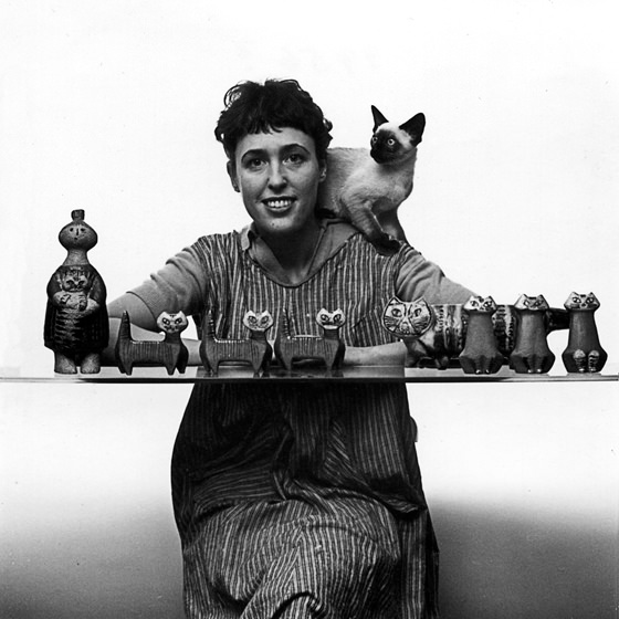 Lisa Larson with a collection of her cat figures with a siamese cat on her shoulder