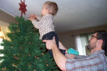 Helping daddy place the star on the tree. 2012.