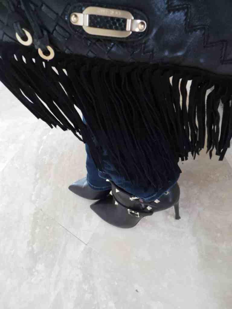 Botines y cartera con flecos ayudan a lucir a la moda aun con un look rockero