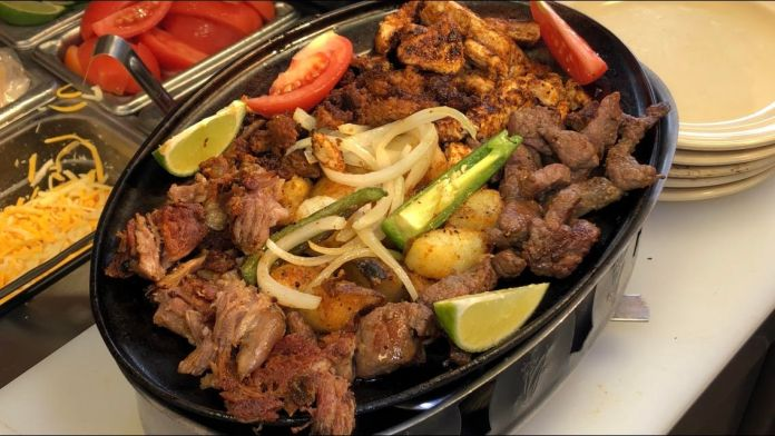 Parrillada is a mouth watering mountain of meat, filled with carne asasda, chicken, chorizo, grilled onions, jalapenos, potatoes and carnitas.