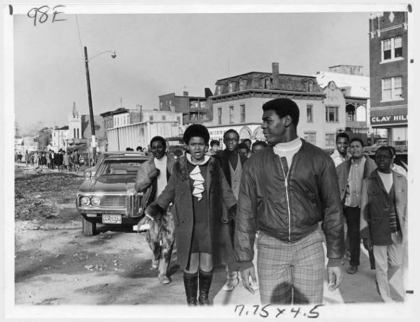 A group of black Weaver High School students march on Albany Avenue in Hartford Connecticut in support of the Black Panthers, chatting and smiling as they go.