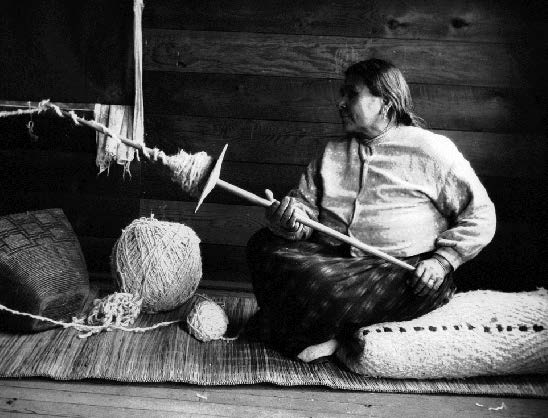 Woman spinning yarn at Coast Salish village of Musqueam, Vancouver, British Columbia. Photograph by Charles F. Newcombe on a field trip with Mary Lois Kissell, 5 December 1915. Royal British Columbia Museum; PN 83.