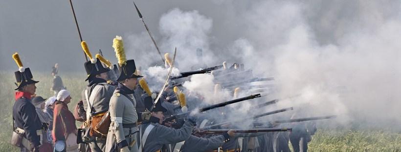 photo d'une reconstitution historique de la bataille de Waterloo avec des hommes habillés en soldats napoléoniens en train de tirer à la carabine
