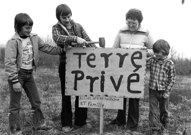 Manifestation par une famille réclamant symboliquement sa terre. Photo du journal L'Évangéline, collection CEAAC, 17 avril 1980.