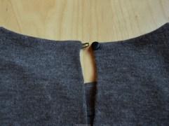 Detail van het knoopje en het lusje die het split in het achterpand sluiten.
