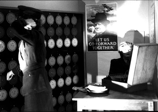 """Un cartel de guerra en el que se puede leer """"Avancemos juntos"""" con la foto del premier británico Winston Churchill cuelga de la pared de una sala en la que un operario manipula una Bombe, la máquina con la que Turing y Welchman consiguieron descifrar parte de los códigos creados por Enigma."""