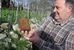 Un veciño de Quintá, na parroquia chantadina de A Grade, amosa os restos romanos atopados na zona / La Voz