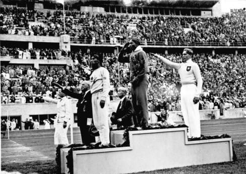 Jesse Owens en un podium de los JJOO de Berlín