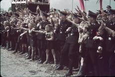 Excited crowds greet a saluting and marching German Fuhrer Adolf Hitler at Fallersleben Volkswagen Works cornerstone ceremony.