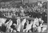 Standing in an open car, Adolf Hitler salutes a crowd lining the streets of Hamburg. (August 17, 1934).