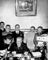Vyacheslav Molotov signs the Molotov-Ribbentrop Pact, a German–Soviet non-aggression pact.