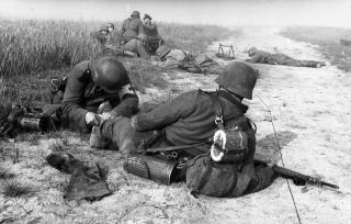 A German Military Medic providing first aid to a wounded soldier.