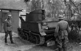 An abandoned Belgian T-13 tank destroyer is inspected by German soldiers.
