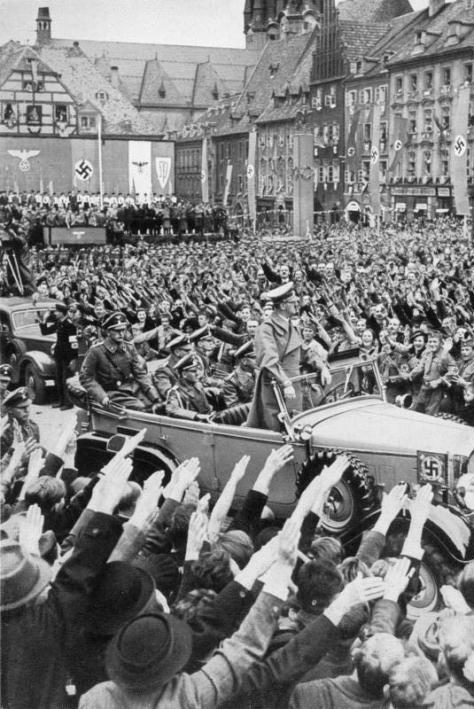 October 1938: Hitler (standing in the Mercedes) drives through the crowd in Cheb (German: Eger), part of the German-populated Sudetenland region of Czechoslovakia, which was annexed to Nazi Germany as part of the Munich Agreement.