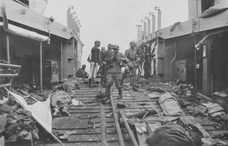 Soldiers inspect a landing craft strewn with the bodies of killed Canadian and British soldiers, Dieppe 1942.