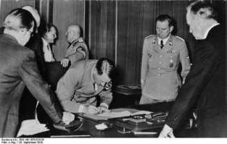 Hitler signing the Munich Accords.