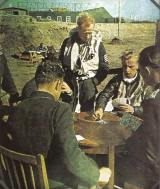 Luftwaffe pilots playing cards in an airfield somewhere in Germany.