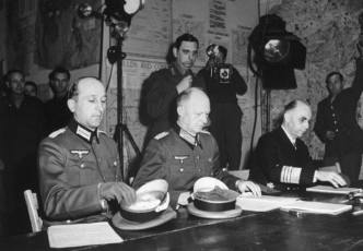 """""""Jodl, wearing Iron Cross low on his left breast, is seated between the major and admiral. With [German Head of State Karl] Donitz's authorization, he has nothing to do but sign the surrender."""""""