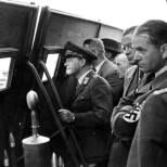 Speer (right, with arms folded and swastika armband) looks on with Field Marshal Erhard Milch (left) during weapons testing.