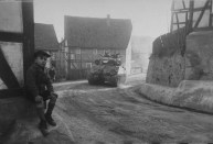 A young German boy sits beside the road as a tank of the U.S. 9th Armored Division passes through his village on its way to Berlin, spring 1945.