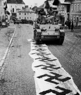 An American tank rolls over a Nazi banner laid out in the street after its crew helped take the town of Lembach, spring 1945.
