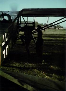 An officer board a Fi 156 C. The aircraft's engine is already running in preparation for takeoff across the horse pasture.