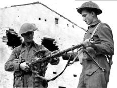Canadian soldiers inspect a captured German MG34 machine gun. With a rate of fire of up to 900 rounds per minute, it fired about twice as fast as its Canadian Army counterpart, the Bren gun.