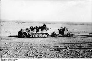 North Africa, towed behind an SdKfz 7. Side outriggers lifted for transport visible behind the gun shield.