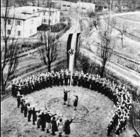 Relocated children salute the flag at an unidentified Kinderlandverschickung camp, date unspecified.