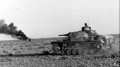 Afrika Korps Pz Mk III advances past a vehicle burning in the desert, April 1941.