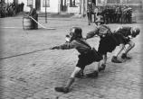 Hitler Youth boys play tug of war while wearing gas masks, 1933.