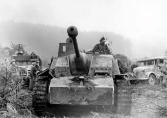 A StuG III Ausf. G during the Ardennes Offensive, 1945. In the background to the left of the StuG is a captured American M3 half track.