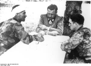 Max Wünsche(left), Fritz Witt(center), Kurt Meyer(right) at a commanders strategy session on or about 7–14 June 1944 in the vicinity of Caen, France.