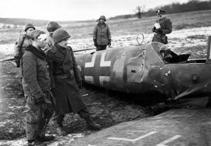 Crash site of a Messerschmitt Bf 109G during Operation Bodenplatte. The man in the front is the pilot.