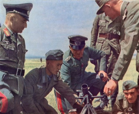 Tatar helps in firing a German mortar. The general in the center is Generalleutnant Heinz Hellmich, while the general at far left is Generalmajor Hellmuth Nickelmann.