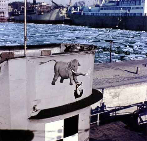 "It is U-34, wearing the emblem consisting of an elephant stepping the head of Winston Churchill, England's First Sea Lord. Beneath it is the training boat emblem. Exactly when the elephant emblem was introduced is not clear, for the boat is believed to have worn the ""Raben Huckebein"" (Raven Huckebein) emblem during its seven operational patrols."